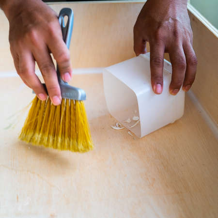 cleaning and home concept - close up of male brooming wooden floor with small whisk broom and recycled milk boxes as dustpan