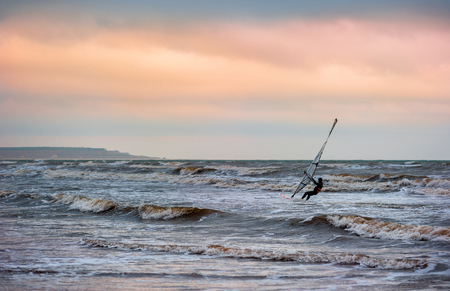 Man on windsurfing in the distance  Evening sky, sea after a gale  photo