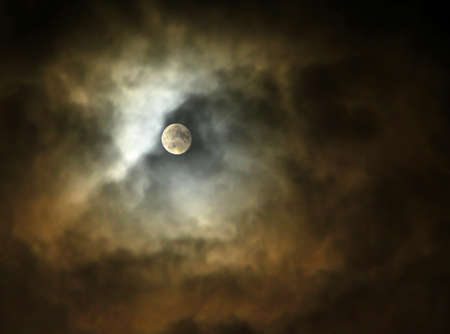 The dramatic Full Moon is between the night storm clouds. Night sky with bright moon among colorful illuminated clouds.