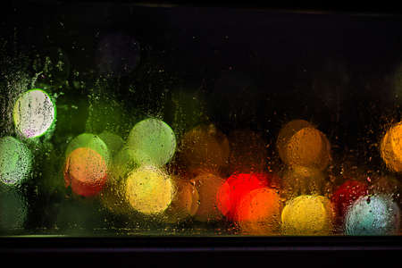 has been: Blurry colorful city lights can be seen through a window which has been rained on