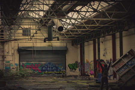 abandoned warehouse: A man makes the peace symbol with both hands in an abandoned warehouse covered in graffiti Editorial