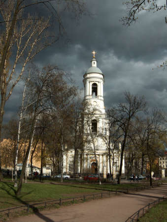 Black clouds over white Orthodox cathedral in the spring photo