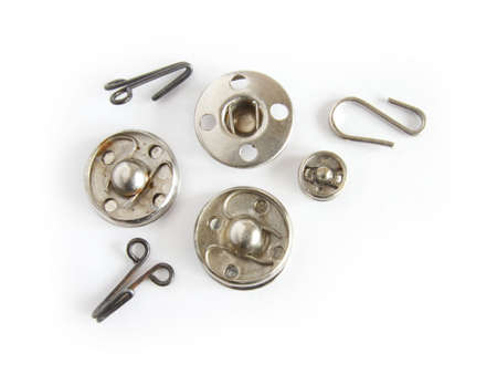 Metallic buttons and hooks. Objects over white.
