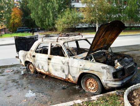 Burned up white car parked on the street