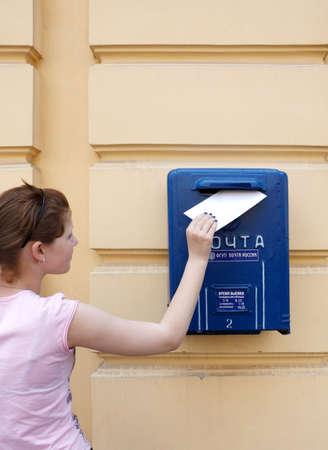 Girl puts the letter into mail box