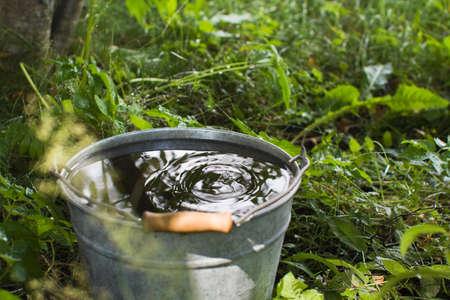 Metal bucket with the rain water Stock Photo
