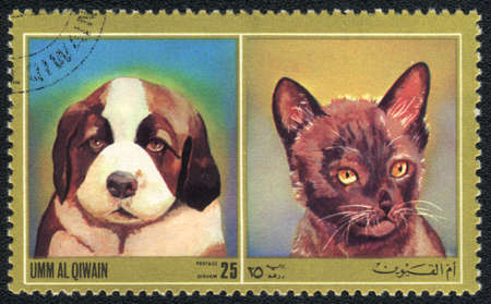 Umm al Qiwain - CIRCA 1971: A stamp printed in Umm al Qiwain shows cat and dog from series: Different breeds of dogs and cats, circa 1971 photo