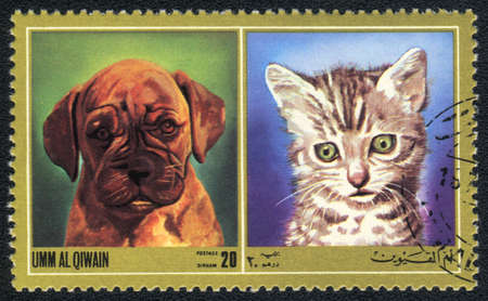 Umm al Qiwain - CIRCA 1971: A stamp printed in Umm al Qiwain shows cat and dog from series: Different breeds of dogs and cats, circa 1971 Stock Photo - 10516643
