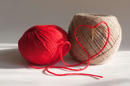 A couple of balls of yarn with a needle and a red heart