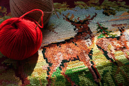 Old embroidery with a deer, and balls of yarn photo