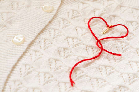 The red thread in the needle in the shape of a heart on a white blouse photo