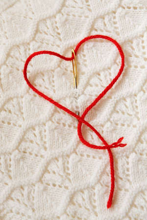 darn: The red thread in the needle in the shape of a heart on a white knitted fabrics