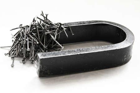 magnetismo: Imán con pila de clavos en el fondo de plástico ligero Foto de archivo