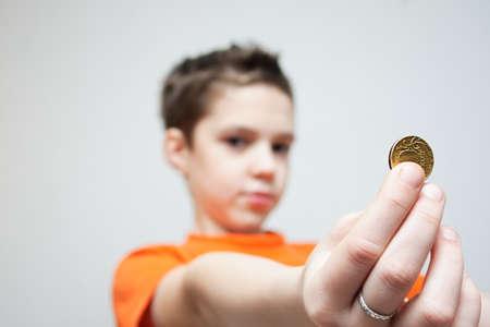 Boy holding a copper coin  A small depth of focus photo