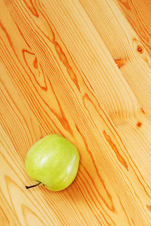 One green apple on smooth boards. View from the top Stock Photo - 13424710