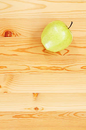 Green apple on a smooth wooden surface. View from the top Stock Photo - 13496123