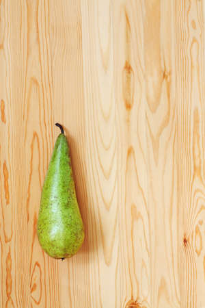 oblong: Green pear on a light wood  View from the top