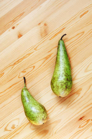Two pears  lying on a wooden surface  photo