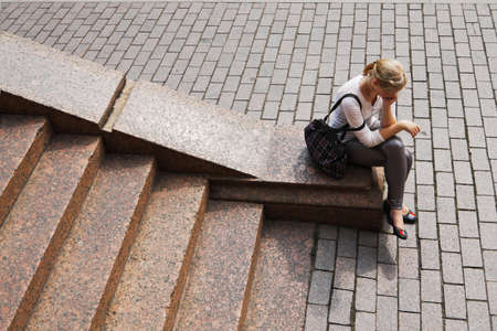 A young girl sits on the granite steps and pondered photo
