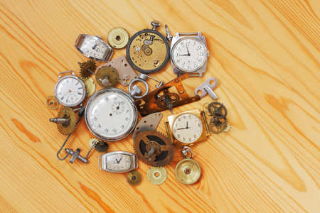 The old mechanical clock and the details of their mechanisms lie on a wooden surface photo