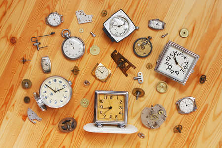 The old alarm clocks, wrist watches, stop watch and clock parts lie on a wooden surface photo