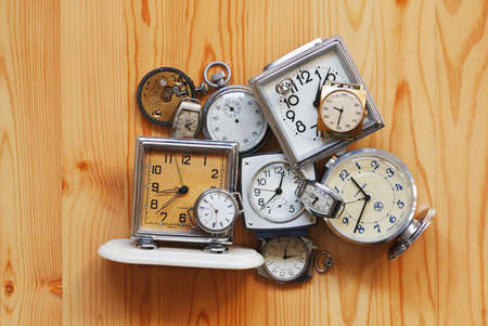 The old alarm clocks, watches, stop watch lying on a wooden surface Stock Photo