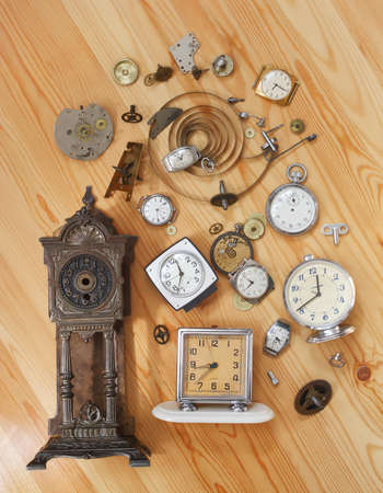 The old alarm clocks, watches and details of clock on a wooden surface photo