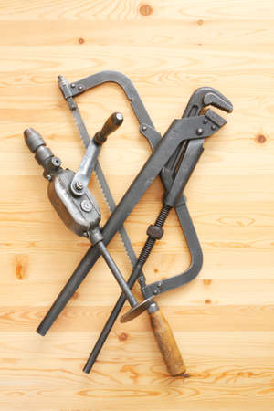 Hacksaw, adjustable spanner and drill on the  wooden surface photo