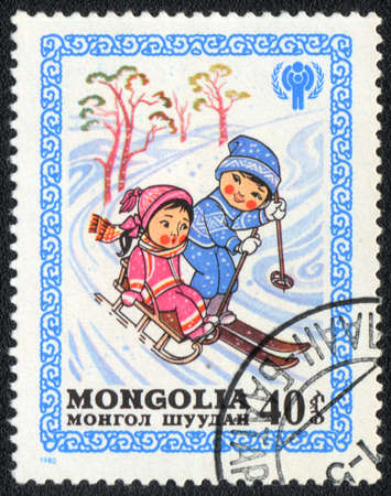 MONGOLIA - CIRCA 1980: A stamp printed in MONGOLIA   shows Boy and girl slide down on sleds and skis, from series Happy childhood, circa 1980  photo
