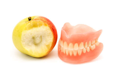A false teeth and apple isolated on white background photo