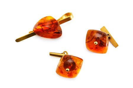 cuff link: Amber cuff links and clip for necktie isolated on white background.  Stock Photo