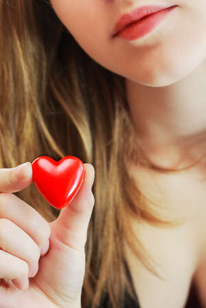 Girl holds in her hand a small red heart. photo