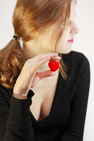 Girl in black cardigan holds in her hand a small red heart photo