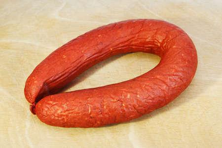 Smoked sausage Krakovskaya on wood board Stock Photo - 16380185