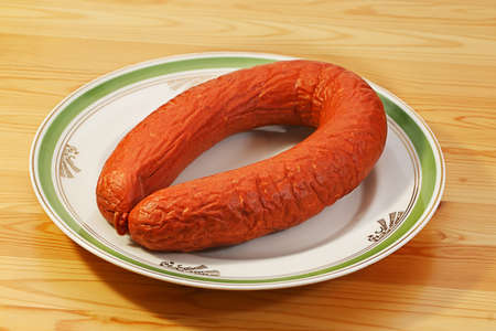 unharmed: Wheel of half- smoked sausage on dinner-plate Stock Photo