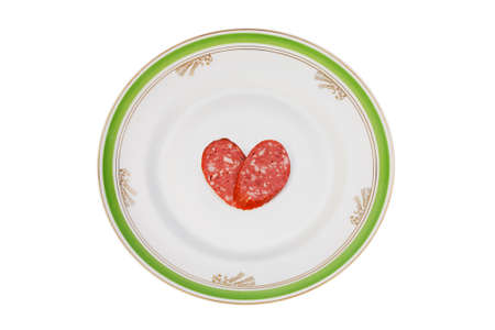 Slices of sausage in the form of a heart on a old dinner plate photo