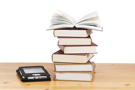 A pile of books and e-book on wood table against a white background photo