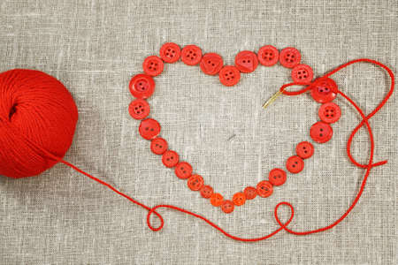 Heart in shape of red buttons, needle and yarn City of St  Petersburg was called Leningrad in USSR Stock Photo - 17527536