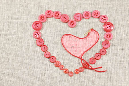 Pink buttons in form of the heart and needle with thread on light fabric   City of St  Petersburg was called Leningrad in USSR Stock Photo - 17527534