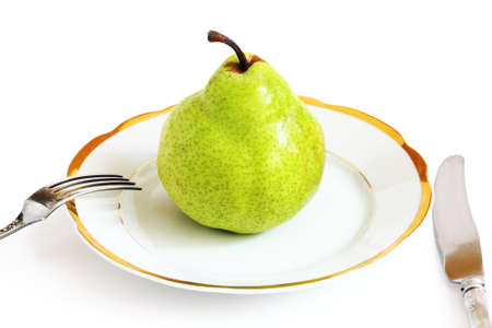 Big green pear on a white plate isolated on white background photo