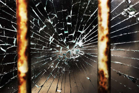 Cracked glass behind bars photo