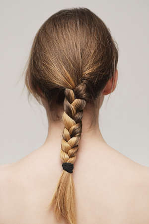 Blonde braid on the open back of a girl