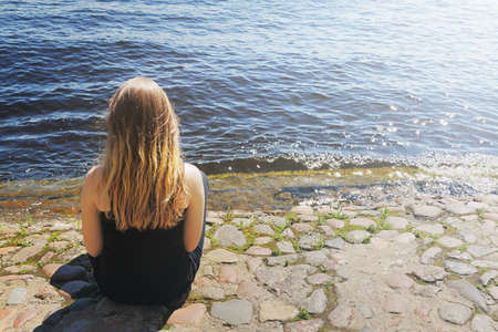 blond hair: Young girl with blond hair sits by the river
