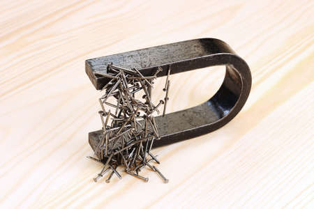 Magnet with  steel nails on wooden background Stock Photo