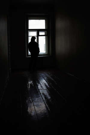 Lonely woman at the window in empty old room photo