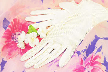 Vintage white gloves and artificial flowers of jasmine on flowered silk photo