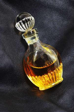 Perfume on dark leather background. Low-key lighting photo