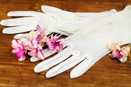 Old white gloves and artificial flowers on wooden background photo