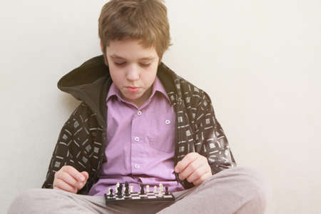A boy plays with himself chess photo