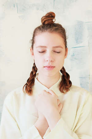 appease: The quiet girl stands with closed eyes and folded hands